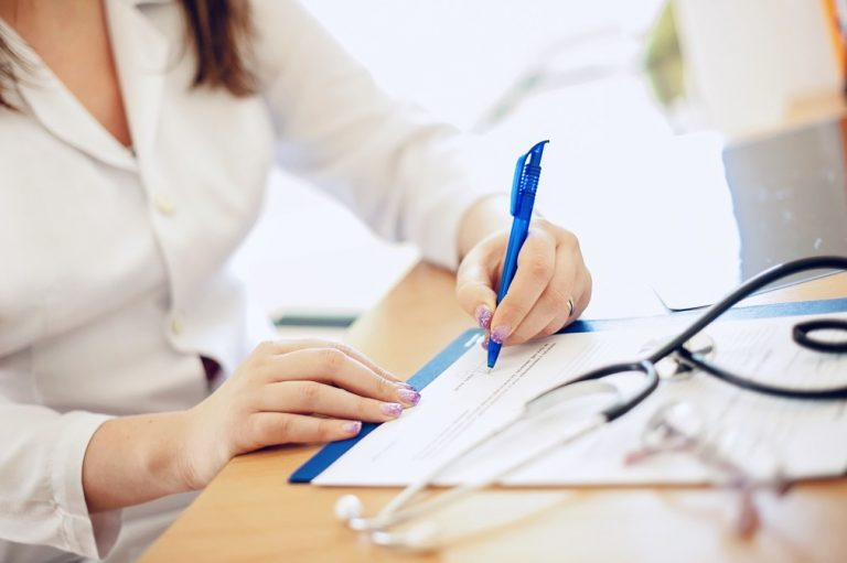 aposentadoria de médico - pessoa sentada assinando um documento e com om estetoscópio na mesa